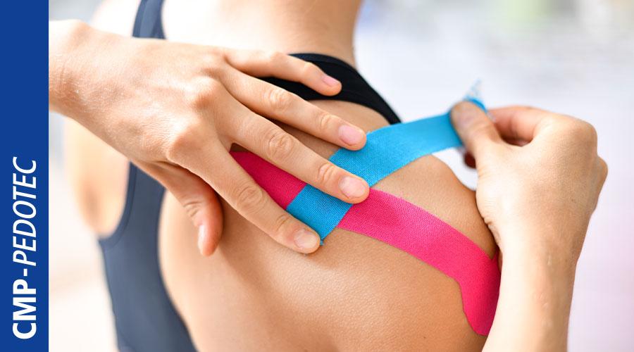 Frau wird mit elastischem Kinesio-Tape im Rückenbereich versorgt.